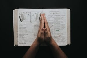 person-placing-hands-on-bible-2258251